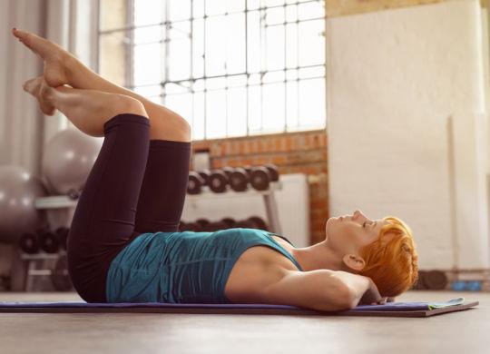 frau im fitness-studio liegt mit geschlossenen augen auf einer matte und ruht aus